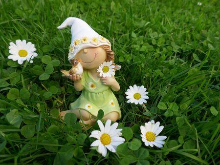 enano: La pequeña muchacha enana con un pájaro en sus manos se sienta en un prado verde