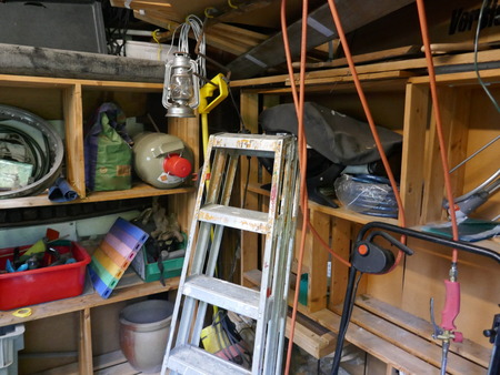 Ladder and tools in a messy storeroom