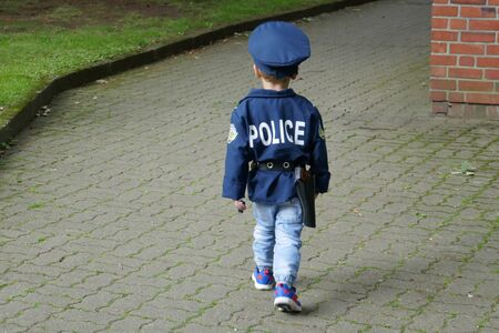 Little boy, disguised as a policeman, from behind