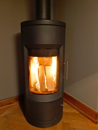A modern, burning, black, iron stove with chimney is in the living room in a corner Modern burning stove in a corner at home