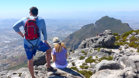 A young couple with backpack and sun has climbed Table Mountain and looks down on Cape Town.