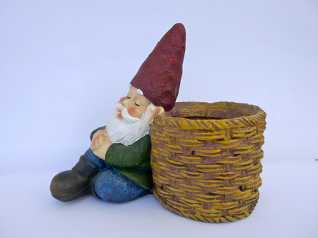Asleep garden gnome sitting on a brown basket. Isolated on white background Stock Photo