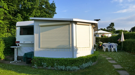 Caravan with a fixed porch made of awning fabric, glass sliding windows and blinds on a German camp site. Comfortable and well maintained. The blinds are closed.