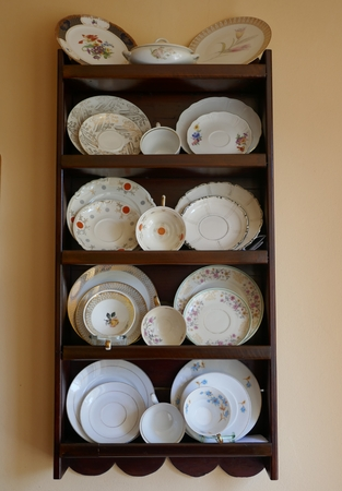 Porcelain dishes, cups and plates, old collection cups in a brown mahogany wooden shelf
