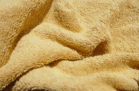 golden brown background of soft, fluffy, terry cloth or plusch fabric