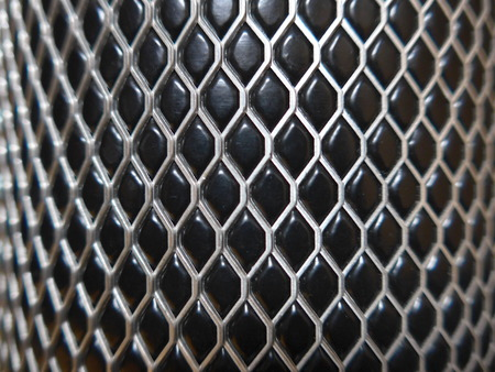 Bent metal wire on black, shiny background, metallic rhombs, closeup, modern pattern, texture,