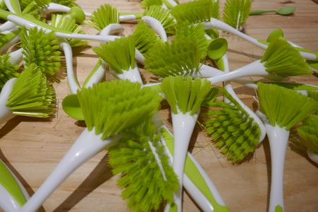 Many white dishwashing brushes with green bristles to sell