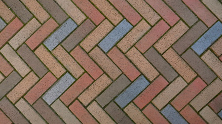 Multi-colored brick pavement, herringbone pattern, on a sidewalk. Background, texture, close-up
