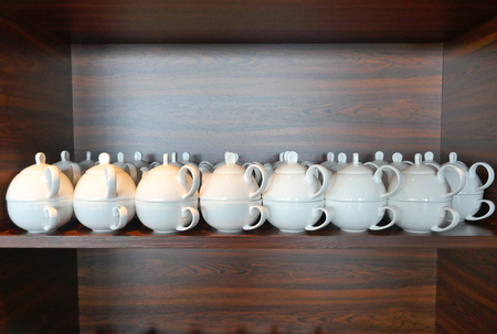 Teapot and cup, set for one person, a small white teapot and a teacup. Tea for One, many white stacked porcelain tea cups and small teapots in a dark brown wooden shelf