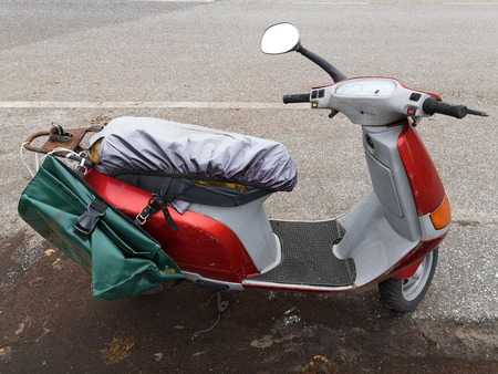 Old dirty italian scooter at the roadside