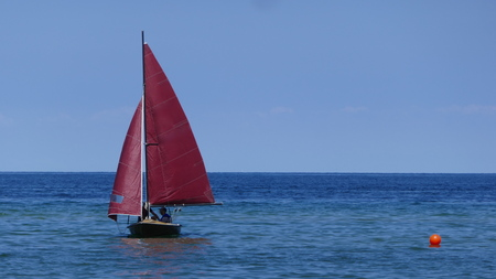 Small sailboat on an old sailing dinghy with dark red sails floats in the blue sea