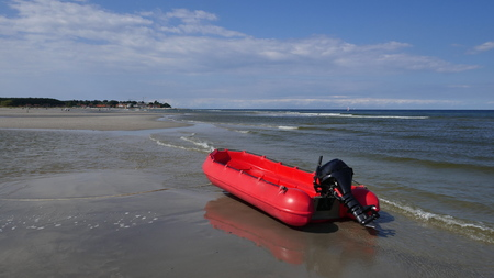 Lonely red rubber dinghy with outboard motor at low tide on the baltic sea Stock Photo