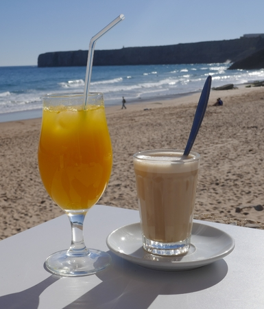 Freshly squeezed orange juice and a glass of latte in a small beach bar overlooking the sea