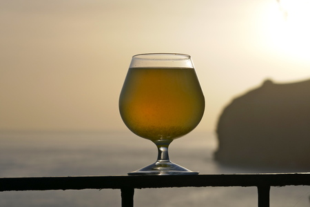 A glass of poncha at Sunset on Madeira with stunning views of the Rocky Coastline. Poncha is a traditional alcoholic beverage from the island of Madeira