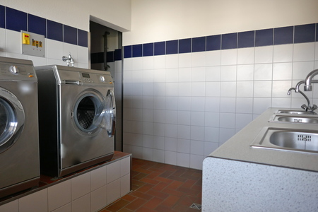 Automatic washing machines and stainless steel sinks in the utility room of a campsite in Schleswig-Holstein, Germany, Europe Stockfoto