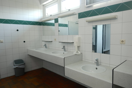 Modern sanitary facilities in a public building, Germany, Europe The public, clean sanitary room has a large selection of sinks with mirrors, hairdryers, sinks and shower stalls