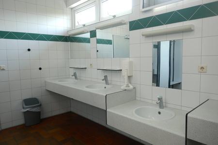 Moderne Sanitäranlagen in einem öffentlichen Gebäude, Deutschland, Europa Der öffentliche, saubere Sanitärraum verfügt über eine große Auswahl an Waschbecken mit Spiegel, Föhn, Waschbecken und Duschkabinen