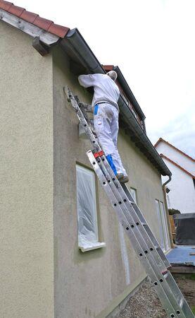 Vista trasera de un pintor de pie sobre una escalera y acariciando la pared exterior de una casa con un rodillo de pintura.