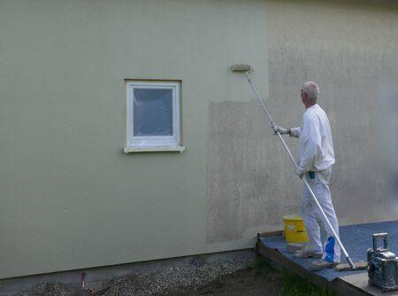 Vue arrière d'un peintre caressant le mur extérieur d'une maison avec un rouleau à peinture sur une longue tige