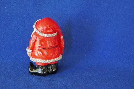 Santa Claus. Nicholas. Christmas time. A cute little gnome in santa claus costume and red bonnet. Rear view. Close up, isolated on blue background. (Not copyrighted)