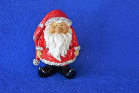 Santa Claus. Nicholas. Christmas time. A cute little gnome wearing santa claus costume and red bonnet. Close up, isolated on blue background. (Not copyrighted)
