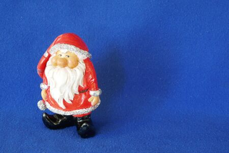 Santa Claus. Nicholas. Christmas time. A cute little gnome in santa claus costume and red bonnet. Close up, isolated on blue background. (Not copyrighted) Stockfoto