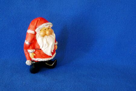 Santa Claus. Nicholas. Christmas time. A cute little gnome wearing santa claus costume and red bonnet. Side view. Close up, isolated on blue background. (Not copyrighted) Stockfoto