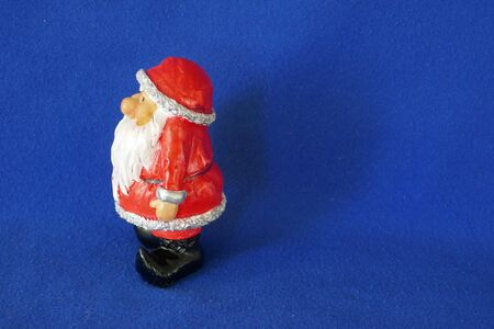 Santa Claus. Nicholas. Christmas time. A cute little gnome in santa claus costume and red bonnet. Side view. Close up, isolated on blue background. (Not copyrighted)