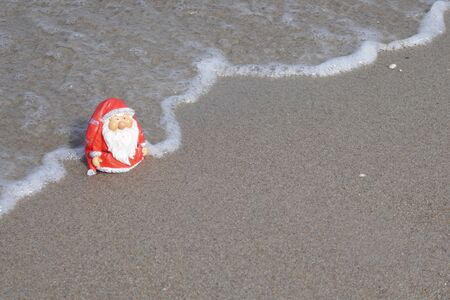 Christmas by the sea. Have fun at the beach holiday with Santa Claus.Little garden gnome in Santa Claus costume goes on vacation in the tropics and takes a bath ((Not copyrighted))