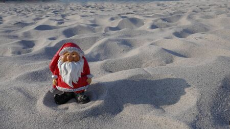 Christmas by the sea. Have fun at the beach holiday with Santa Claus. Little gnome in Santa Claus costume goes on vacation in the tropics (Not copyrighted) Zdjęcie Seryjne - 130686032