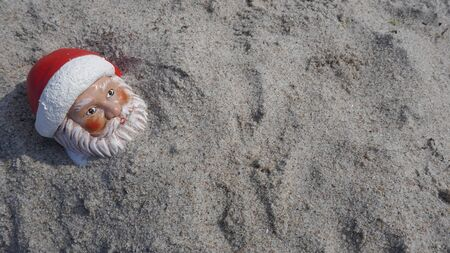 Christmas by the sea. Little gnome with Santa has gone on vacation in the tropics and takes a sand bath (Not copyrighted) Stockfoto