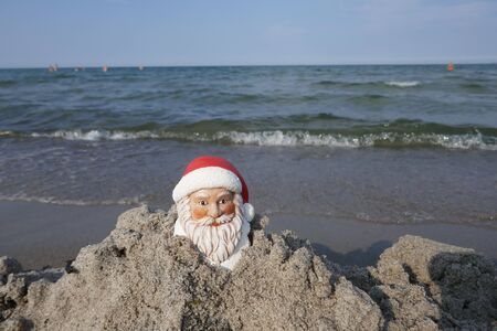 Christmas by the sea. Have fun at the beach holiday with Santa Claus Zdjęcie Seryjne - 130686043