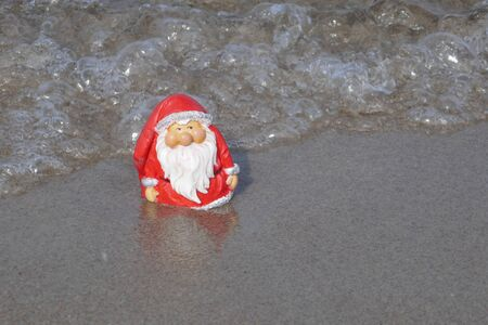 Christmas by the sea. Have fun at the beach holiday with Santa Claus.Little garden gnome in Santa Claus costume goes on vacation in the tropics and takes a bath (Not copyrighted) Stockfoto