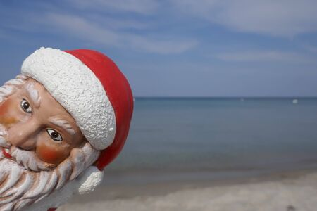 Christmas by the sea. Santa Claus looks around the corner. Have fun at the beach holiday with Santa Claus. Not copyrighted Stockfoto