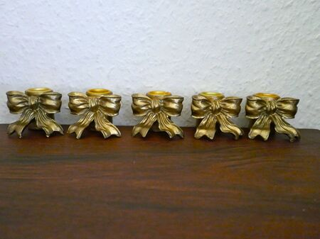 Five antique golden candlesticks decorated with bows on a mahogany shelf in front of a bright wall.
