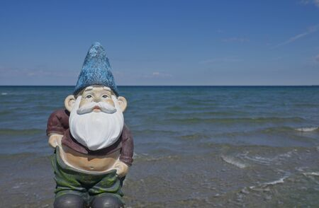 Garden gnome with slipping trousers and belly in front of the ocean (Not protected by copyright)