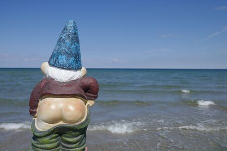 Garden gnome with bare bottom in front of the ocean (Not protected by copyright)