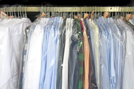 Freshly cleaned mens shirts and ladies blouses in a dry cleaning, hung on hangers and protected by plastic film. Ready for pick up Stock fotó