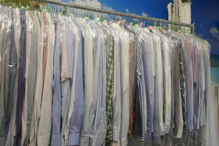 Freshly cleaned mens shirts and ladies blouses in textile cleaning, hung on hangers and protected by plastic film. Ready for pick up Stock fotó