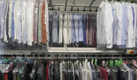Freshly cleaned men's shirts and ladies blouses in textile cleaning, hung on hangers and protected by plastic film. Ready for pick up