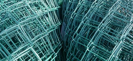 Wire mesh fence, green, rolled up. Close up, texture, background, Stock Photo