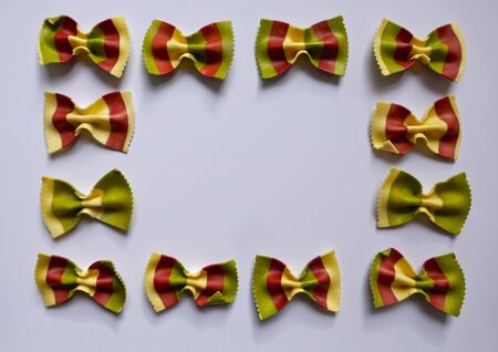 Colorful Pasta, Loop Noodles, Italian Pasta. Twelve farfalle in a row, side by side, one below the other, in front of white background