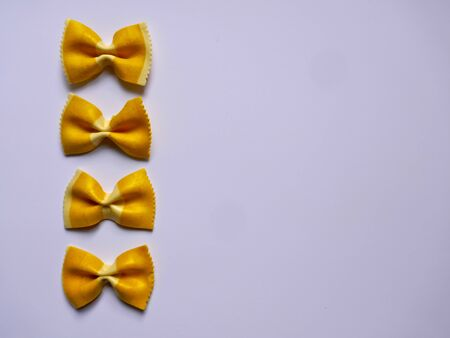 Colorful Pasta, Loop Noodles, Italian Pasta. Four yellow farfalle in a row, one below the other, in front of white background