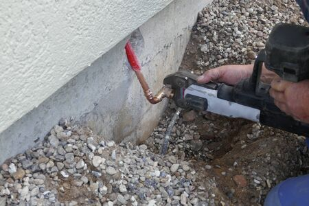 Plumber at work.Installation of an outdoor tap Installer closes water pipe with crimping pliers on the construction site