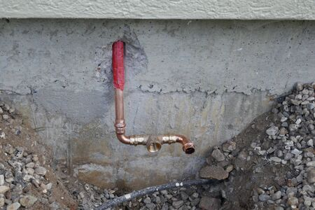 Faucet on a house wall with adapter for a garden hose