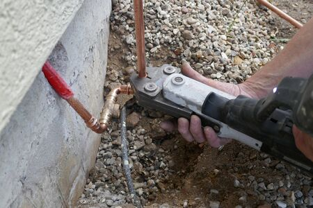 Installation of an outdoor tap. Installer closes water pipe with crimping pliers on the construction site