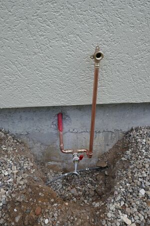 Installation of an outdoor tap on a house wall. Faucet on a house wall with adapters for a garden hose