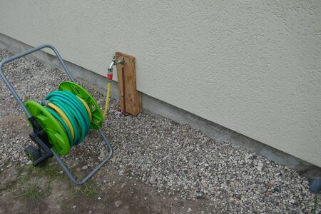 Hose trolley with a rolled-up garden hose on a cold water pipe after installing on outdoor faucet. Stok Fotoğraf