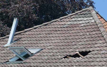 Loch im Dach eines Hauses. Dachschaden. Gebrochenes Ziegeldach nach einem Sturm.