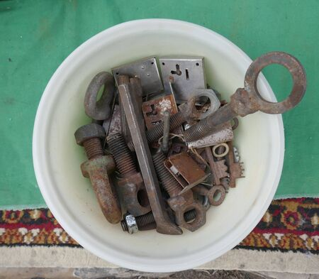 Jumble of old rusty hand tools in a white bowl